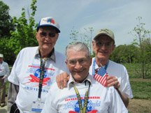 Three smiling veterans in matching shirts